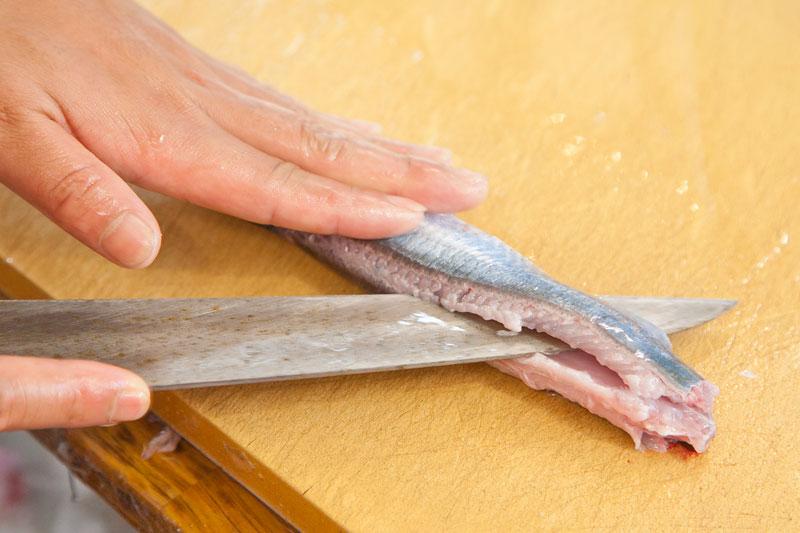 最後にさんまを三枚におろします。秋刀魚を寝かせ、包丁を中骨に添って入れて行きます。