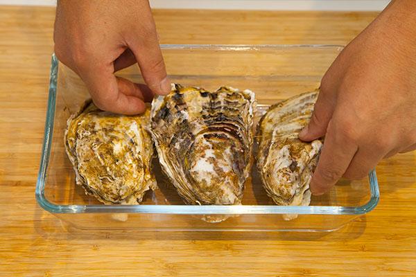 蒸し牡蠣の作り方(電子レンジ編)1 まずは人数分の殻付き牡蠣をお皿の上に並べます。殻付き牡蠣は重なり合わないようにしましょう。