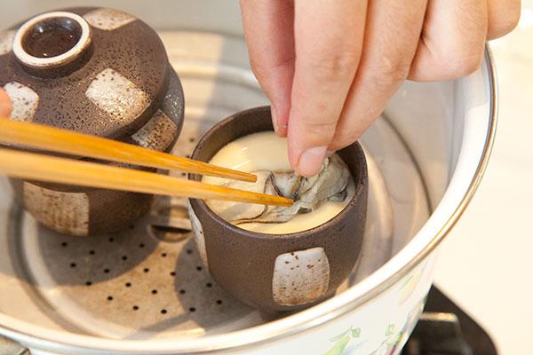 牡蠣の茶碗蒸しレシピ7 3分経ったら蓋を開け表面が薄くまくが張っているのを確認し、その上に牡蠣(かき)を乗せます。