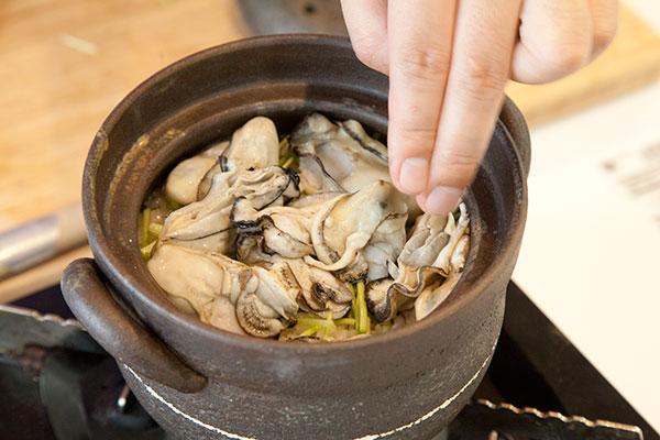 牡蠣ご飯8 ミツバの上に先ほど加熱した牡蠣(かき)をのせ蓋をし10分蒸らし完成です。